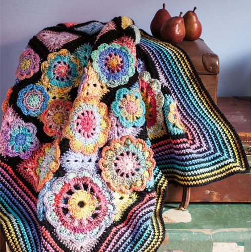 Styled shot of black and rainbow crochet blanket with crochet flowers 5aa9cf611