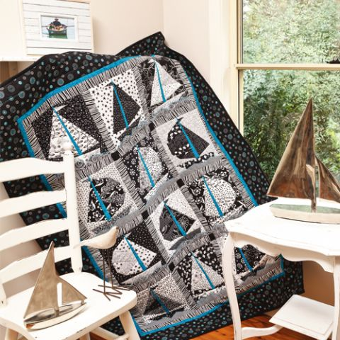 Styled shot of patterned sail boat quilt