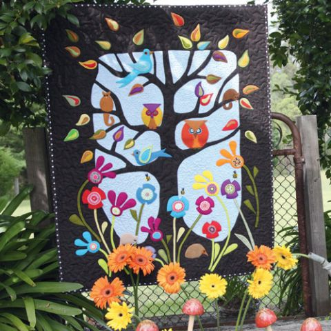 Styled shot of appliqué owl, bird, flower and tree quilt hanging up in garden