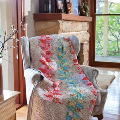Styled shot of patterned patchwork quilt on arm armchair in living room