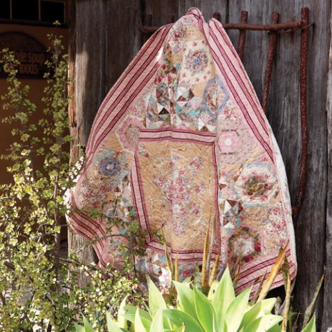 Styled shot of floral hexagon patterned quilt with diamond in the centre hanging in rustic scenery