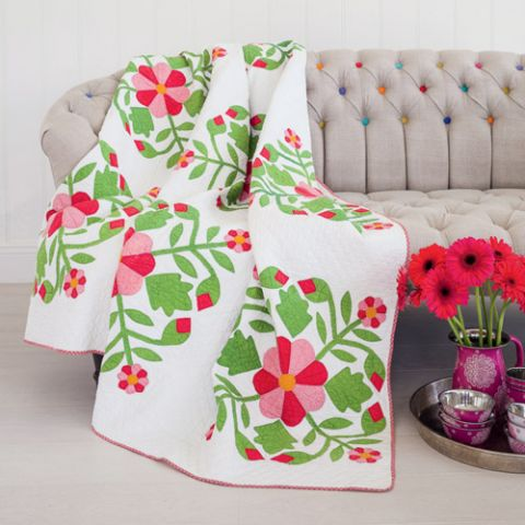 Styled shot of antique appliqué flower quilt on couch with pink flowers