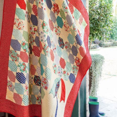 Styled shot of umbrella and rain appliqué and patchwork quilt hanging up with gumboots