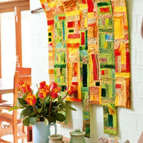 Styled shot of red, yellow and green patchwork wallhanging