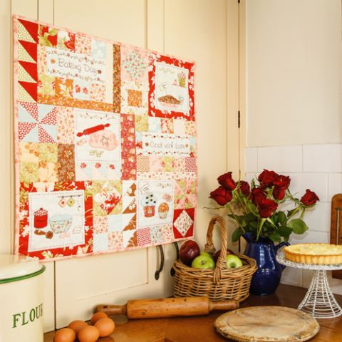 Styled shot of baking themed wallhanging patchwork and embroidery quilt