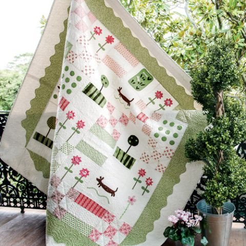 Styled shot of appliqué dachshund and flower patchwork quilt hanging up next to tree and flowers