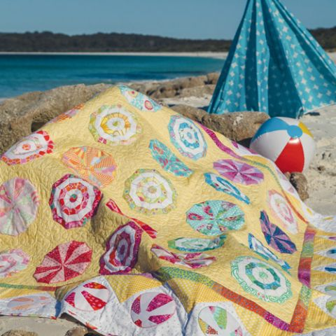 Styled shot of beachballs and umbrellas appliqué and foundation pieced quilt at the beach
