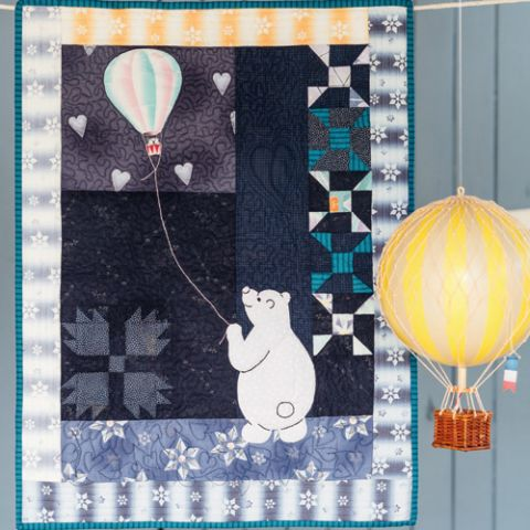 Styled shot of appliqué polar bear and patchwork quilt wallhanging with hot air balloon toy