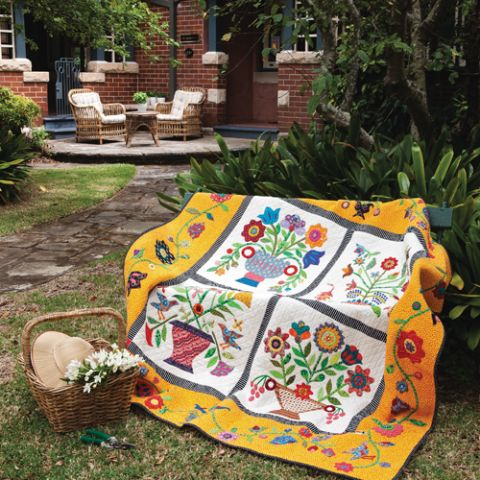 Styled shot of bright and colourful quilt draped over chair outdoors with four different flower scenes