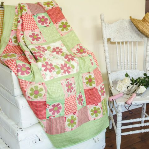 Styled shot of appliqué flower patchwork quilt on suitcases