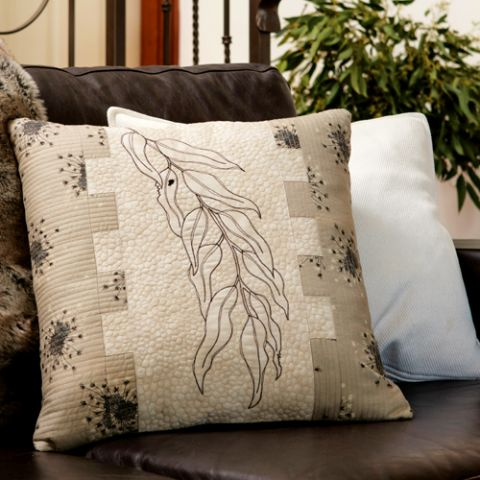 Styled shot of cushion with sewn leaf positioned vertical on lounge