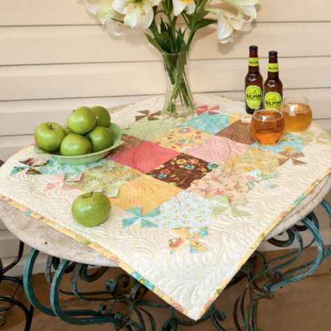 Styled shot of pinwheel mini tabletopper quilt on table with apples and flowers