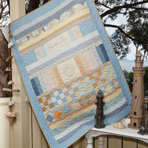 Styled shot of pastel coloured quilt with compass and sea theme outside by the sea