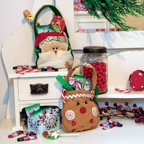 Styled shot of santa and rudolph christmas appliqué and embroidered bags with treats