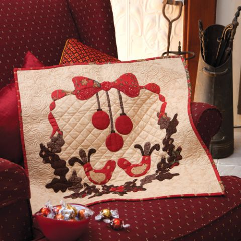 Styled shot of mini christmas appliqué wallhanging quilt on armchair