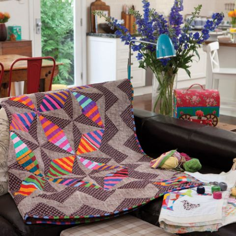 Styled shot of english paper pieced pinwheel and star modern quilt draped over sofa