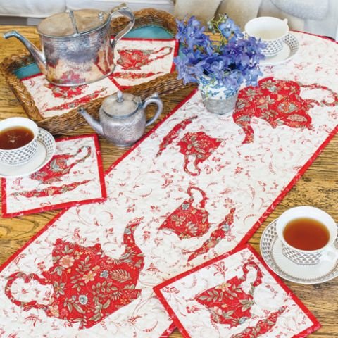 Styled shot of foundation pieced teapot and teacup tablerunner and coasters on table