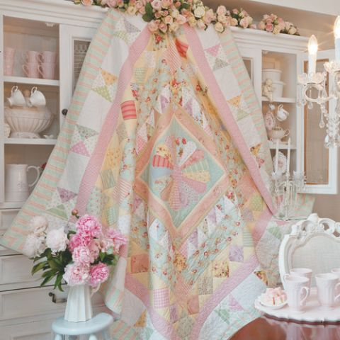 Styled shot of english paper pieced and patchwork medallion quilt hanging up