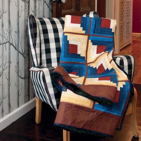 Styled shot of log cabin quilt draped over chair