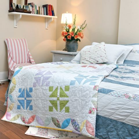 Styled shot of colourful square patterned patchwork quilt draped on bed