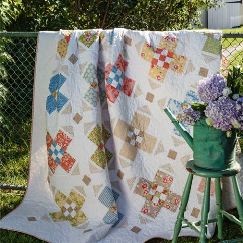 Styled shot of nine patch and cross patchwork quilt draped over fence