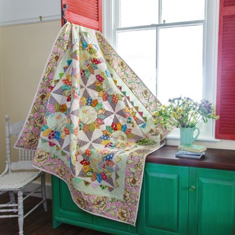 Styled shot of colourful patchwork quilt draped from window over table