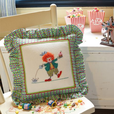 Styled shot of colourful cushion with embroidered clown pouring tea and holding cupcake