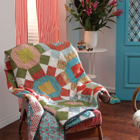 Styled shot of large geometric star patterned quilt draped over chair in living room