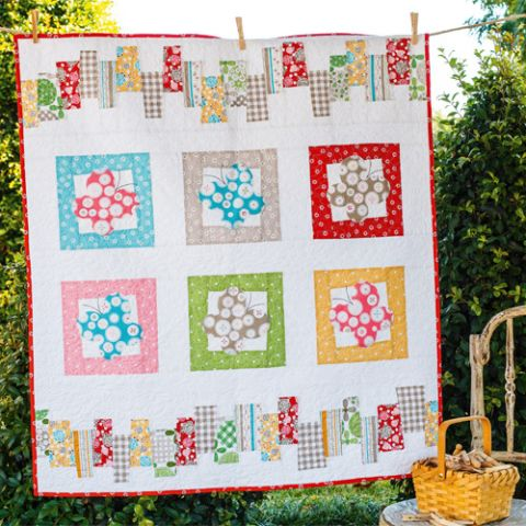 Styled shot of appliqué and patchwork butterfly quilt hanging up in garden