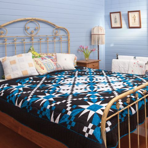 Styled shot of black and blue geometric star quilt in bedroom