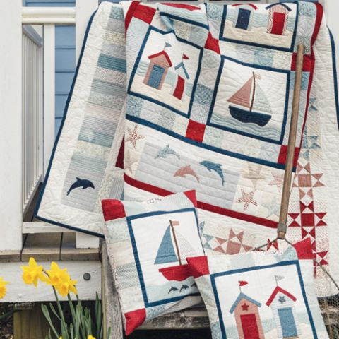 Appliqué and patchwork seaside quilt and cushions styled shot