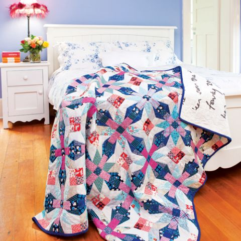 Styled shot of geometric diamond pattern quilt draped over bed