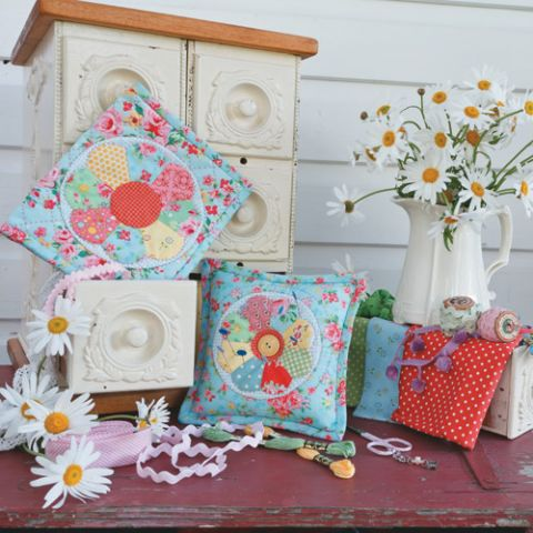 Styled shot of dresden plate pincushion and sewing book with flowers