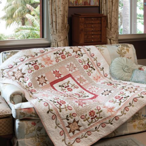 Styled shot of medallion antique style appliqué and patchwork quilt draped over couch