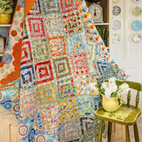Styled shot of spring themed patchwork quilt with diamond pattern and flower edging