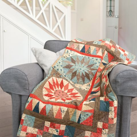 Styled shot of geometric sun patterned quilt lying on couch