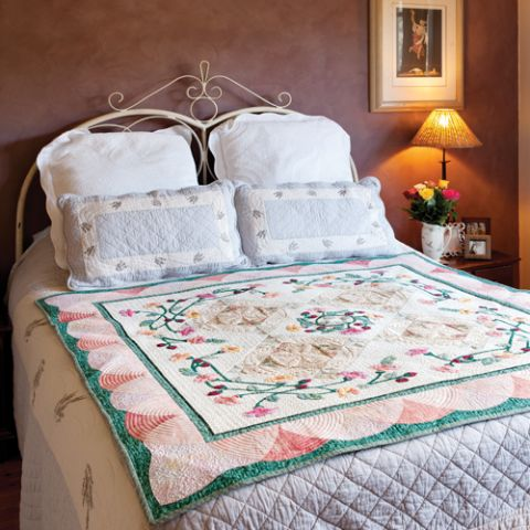 Styled shot of diamond and flower wreath patchwork quilt on bed