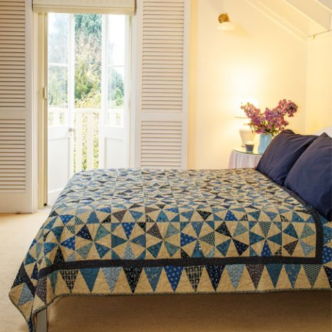 Styled shot of two colour kaleidscope patchwork quilt on bed