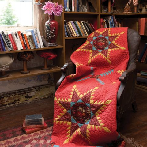 Styled shot of red quilt with 4 large stars draped over chair