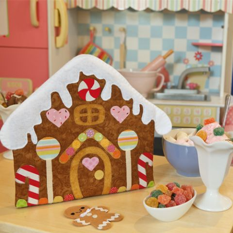 Styled shot of outside of gingerbread house from gingerbread playset with gingerbread man doll