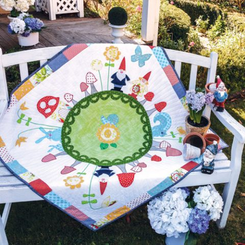 Styled shot of gnome and animal appliqué quilt outdoors with garden gnomes and flowers