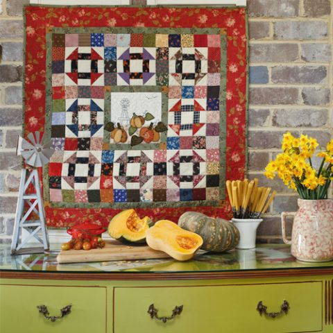 Styled shot of patterned patchwork quilt with pumpkins and windmill