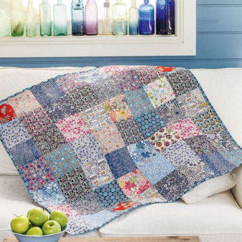 Styled shot of patchwork and heart appliqué quilt on couch