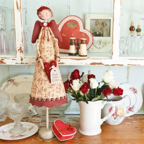 Styled shot of decorative angel doll on display with flowers, photos, glasses and plates