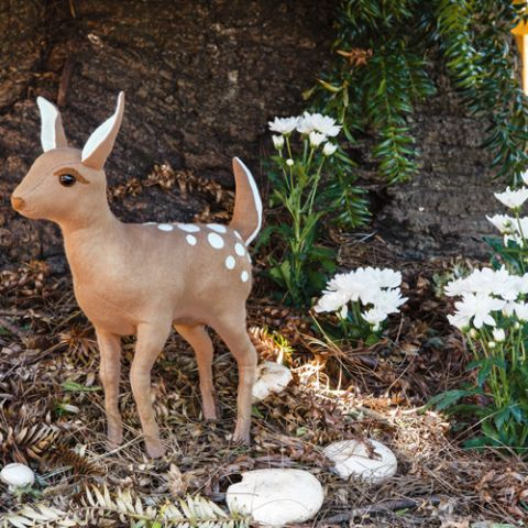 Syled shot of deer plush toy in the forest with mushrooms and flowers