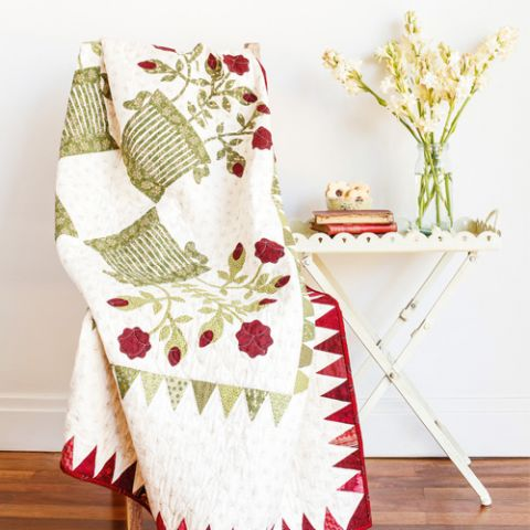Styled shot of appliqué basket and flower quilt draped over chair