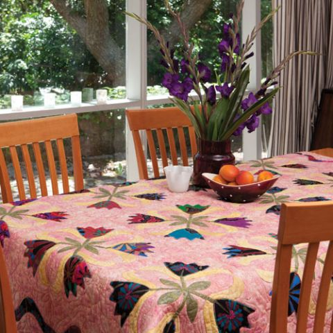 Styled shot of pink lotus flower quilt on table with vase of flowers
