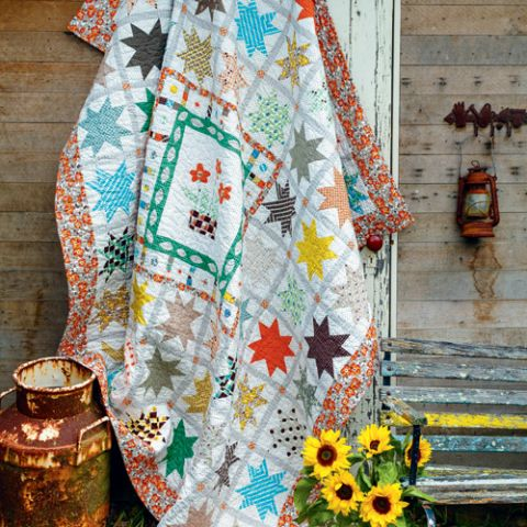 Styled shot of traditional-style appliqué flower and patchwork star block quilt hanging up with sunflowers