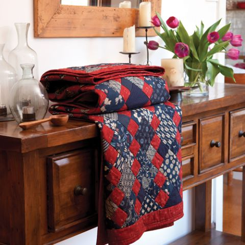 Styled shot of folded blue and red diamond pattern quilt on stylized table