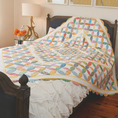 Styled shot of appliqué orange peel quilt on bed
